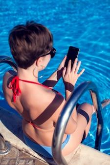 Donna con i capelli scuri corti utilizzando smartphone in piscina in una giornata di sole