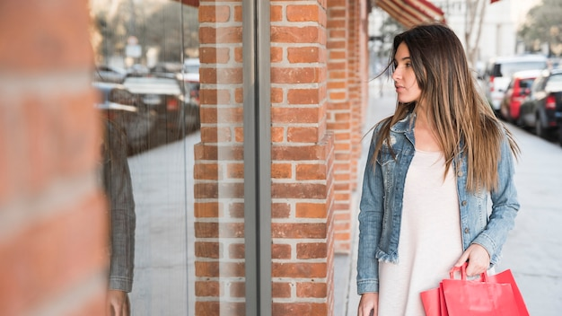 Donna con i pacchetti di acquisto guardando vetrine