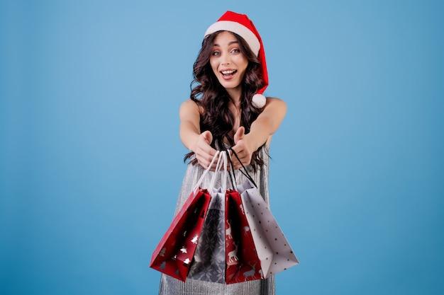 Donna con i presente in sacchetti della spesa che portano il cappello di natale isolato sopra il blu
