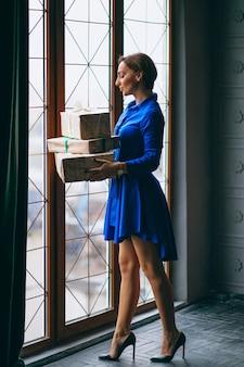 Donna con i regali di natale in piedi vicino alla finestra