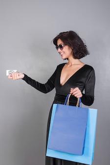Donna con i sacchetti della spesa che danno la carta di credito