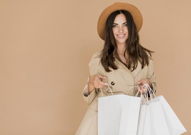 Donna con i sacchetti della spesa che esamina la macchina fotografica