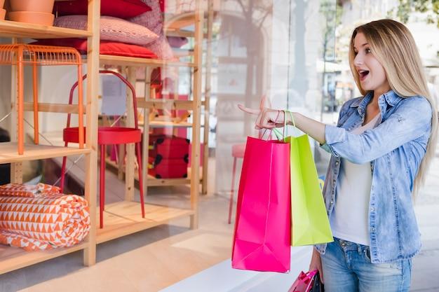 Donna con i sacchetti della spesa che indica dito all'esposizione di un deposito