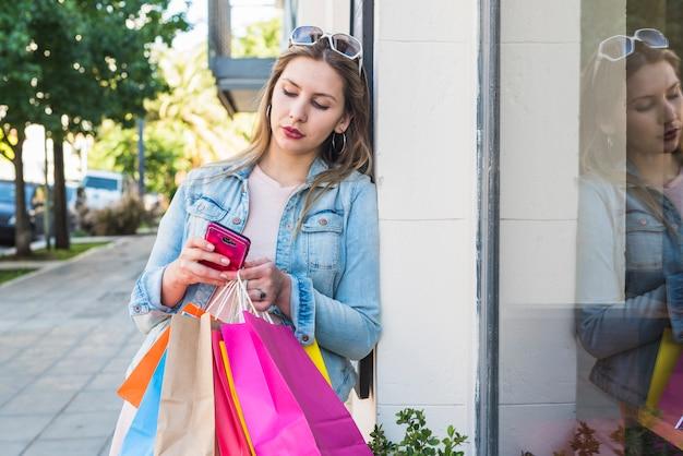 Donna con i sacchetti della spesa che per mezzo dello smartphone fuori