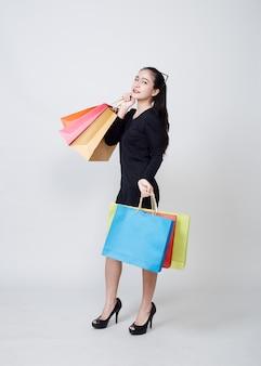 Donna con i sacchetti della spesa che stanno sul bianco