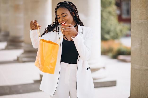 Donna con i sacchetti della spesa gialli