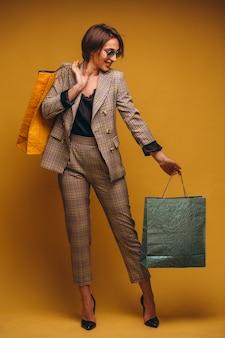 Donna con i sacchetti della spesa in studio su fondo giallo isolato
