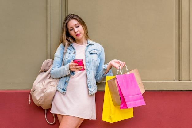 Donna con i sacchetti della spesa luminosi facendo uso dello smartphone alla parete della costruzione