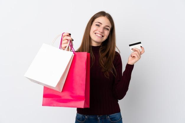 Donna con i sacchetti della spesa sopra la parete bianca isolata