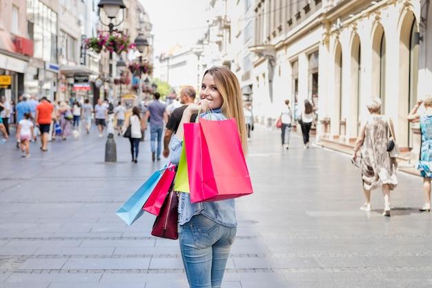 Donna con i sacchetti della spesa variopinti che esaminano macchina fotografica