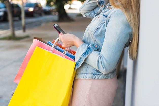 Donna con i sacchetti della spesa variopinti facendo uso dello smartphone