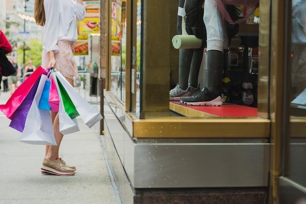 Donna con i sacchetti della spesa vicino alla finestra del negozio