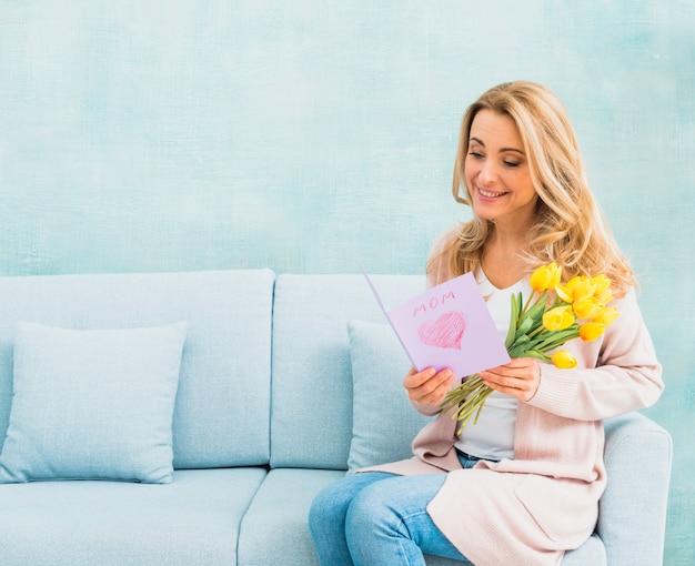 Donna con i tulipani che sorride e che legge cartolina per il giorno del `s della madre