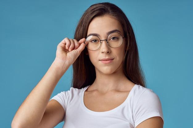 Donna con i vetri che esamina la macchina fotografica, priorità bassa blu