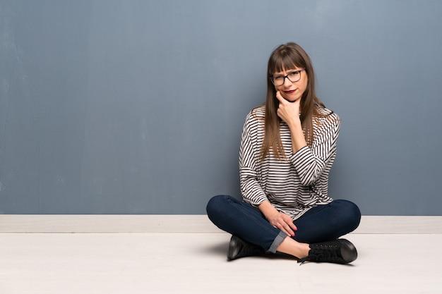 Donna con i vetri che si siede sul pensiero del pavimento
