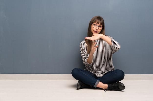 Donna con i vetri che si siedono sul pavimento che fa gesto di time out