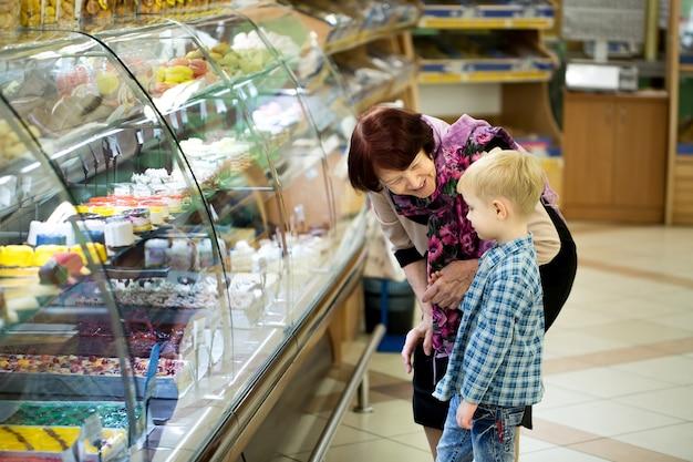 Donna con il bambino che sceglie dessert in supermercato