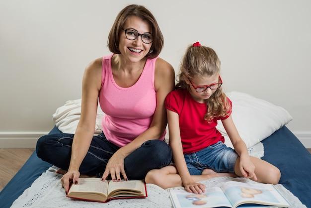 Donna con il bambino della figlia che legge insieme