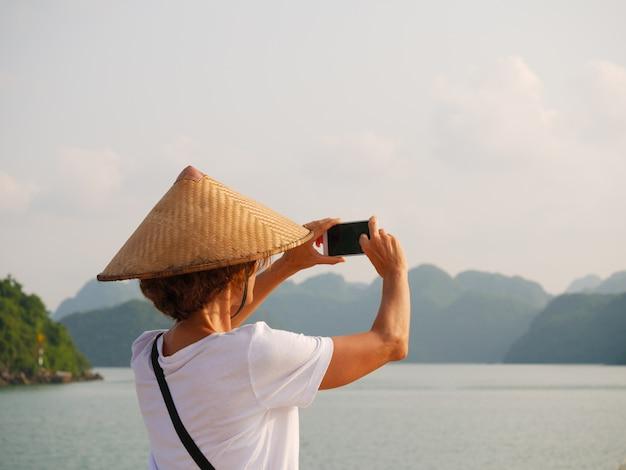 Donna con il cappello tradizionale facendo uso del telefono alla baia di halong, vietnam. turista che viaggiano in crociera tra i pinnacoli di roccia di ha long bay nel mare. signora caucasica divertirsi in vacanza al famoso punto di riferimento.