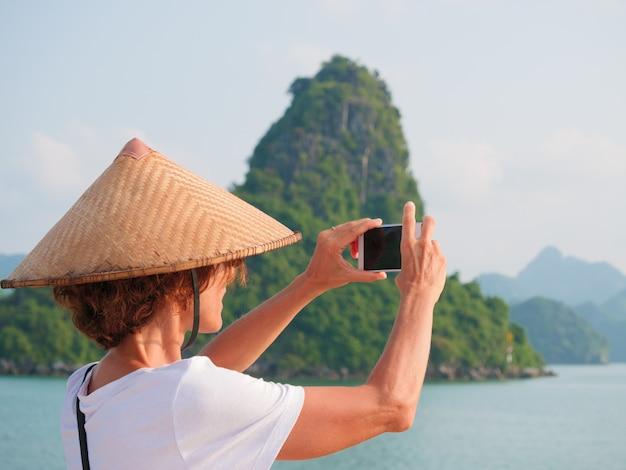Donna con il cappello tradizionale facendo uso del telefono alla baia di halong, vietnam.
