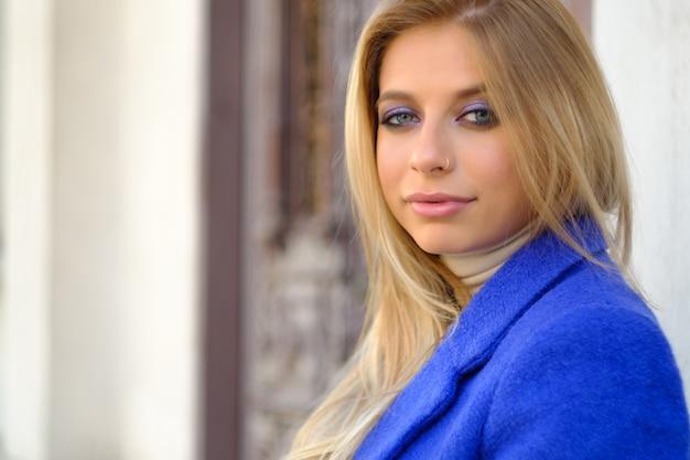 Donna con il cappotto blu sulla strada