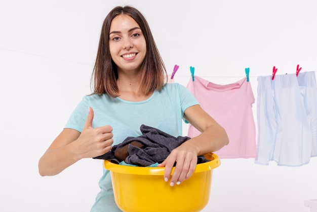Donna con il cestino di lavanderia che mostra approvazione