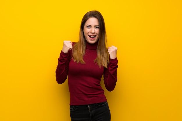 Donna con il collo alto sopra il muro giallo che celebra una vittoria nella posizione del vincitore