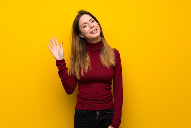 Donna con il collo alto sopra la parete gialla che saluta con la mano con l'espressione felice