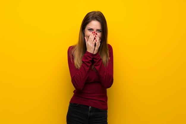 Donna con il collo alto sopra la parete gialla che sorride molto