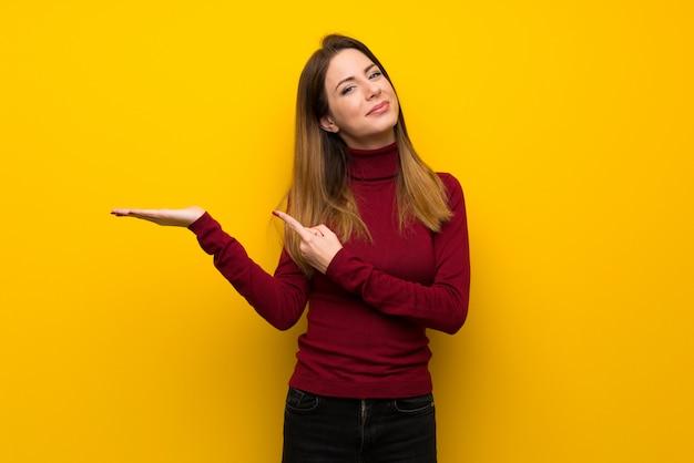 Donna con il collo alto sopra la parete gialla che tiene l'immaginario del copyspace sulla palma per inserire un annuncio