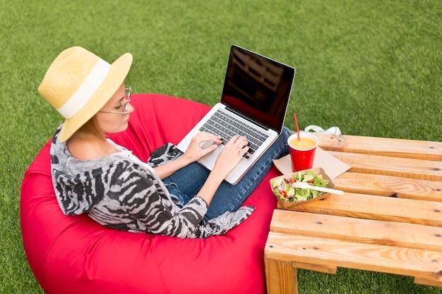 Donna con il computer portatile che esamina insalata