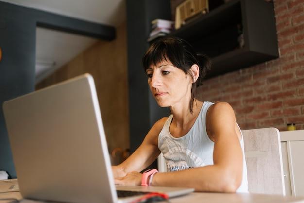 Donna con il computer portatile che lavora a casa