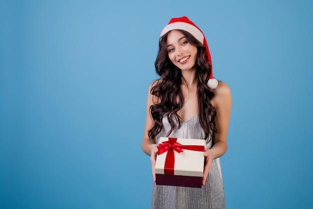 Donna con il contenitore di regalo che porta il cappello di santa