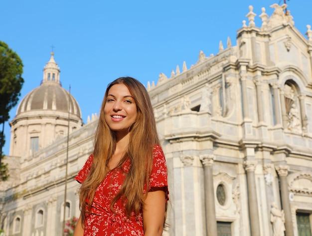 Donna con il duomo di catania in sicilia, italia