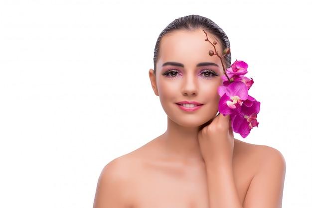 Donna con il fiore dell'orchidea isolata su bianco