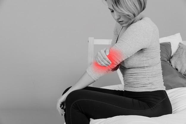 Donna con il gomito dolorante