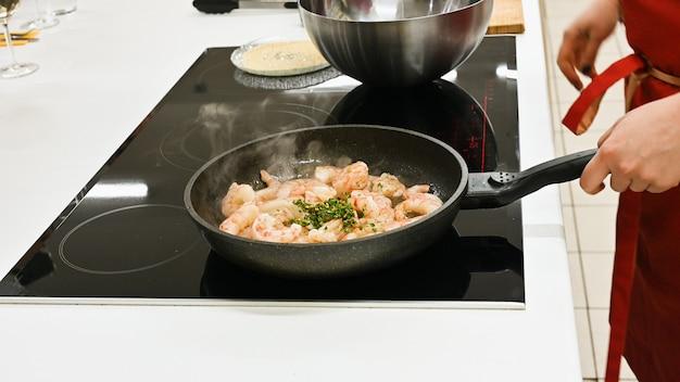 Donna con il grembiule rosso che cucina in una cucina bianca