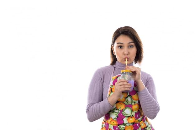 Donna con il grembiule variopinto che beve il succo