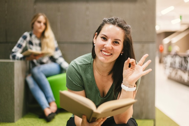 Donna con il libro che fa gesto okay