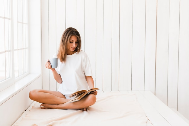 Donna con il libro di lettura della tazza sulla superficie di bianco