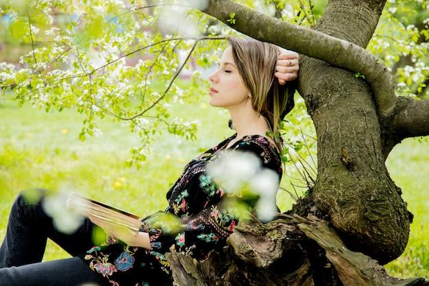 Donna con il libro nel parco di primavera.