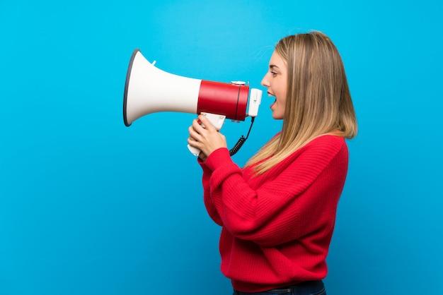 Donna con il maglione rosso sopra la parete blu che grida tramite un megafono