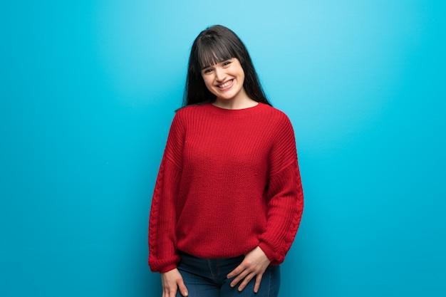 Donna con il maglione rosso sopra sorridere blu della parete