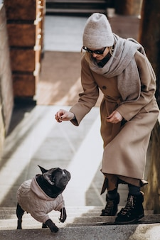 Donna con il suo bulldog francese dell'animale domestico che cammina fuori