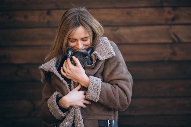 Donna con il suo bulldog francese dell'animale domestico su fondo di legno