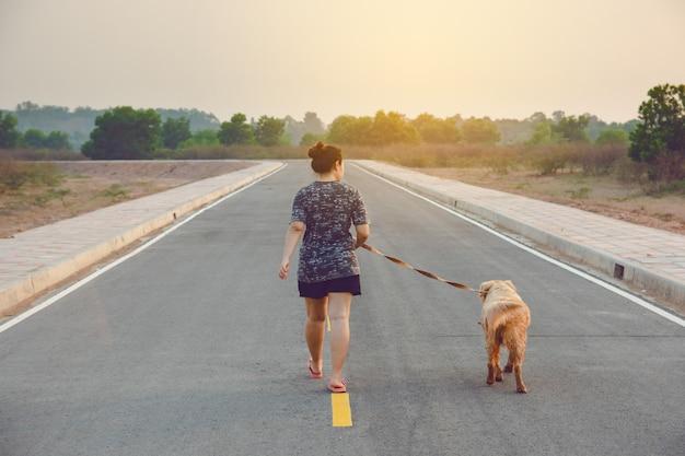 Donna con il suo cane golden retriever che cammina sulla strada pubblica.