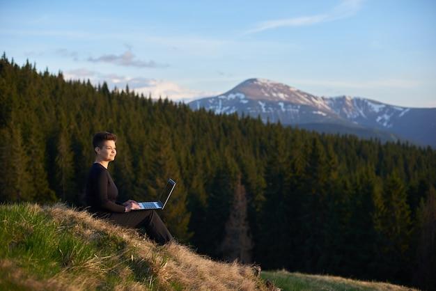 Donna con il suo laptop in montagna