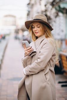 Donna con il telefono nel cappello fuori dalla strada