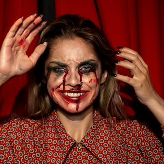 Donna con il trucco di trucco del burlone di halloween con i suoi denti