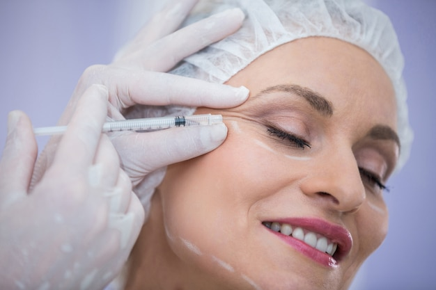 Donna con il viso segnato che riceve iniezione di botox